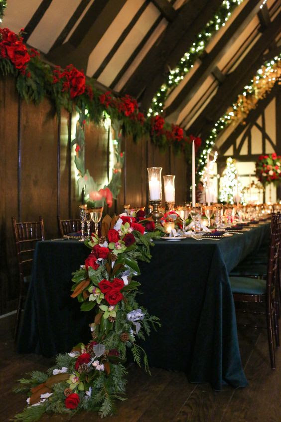 ein cascading Urlaub-inspirierten Tischläufer mit magnolia Blätter, Immergrün, rote Rosen und tannenzapfen für eine festliche Hochzeit