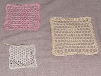 Crochet samples during blocking.  After soaking in hot water these items were shaped and laid to dry on a towel.  Pins hold some examples in the desired shape.