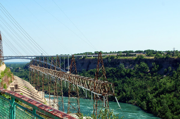 Side view of the Sir Adam Beck 2 Hydroelectric Power Generating Station on the Canadian side of the Niagara River which was put in service in 1954. In the background is the Queenston-Lewiston Steel Arch Bridge which is a replica of the Rainbow Bridge further up river by the Falls.