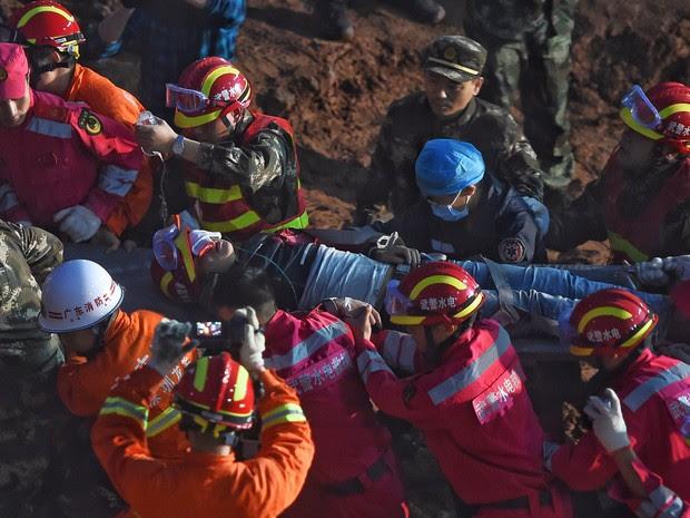 Equipes de resgate retiram jovem de 19 anos que foi encontrado vivo nesta quarta-feira (23) no local de deslizamento de terra que cobriu uma grande área em Shenzhen, na China, no domingo (20) (Foto: Jin Liangkuai/Xinhua News Agency via AP)