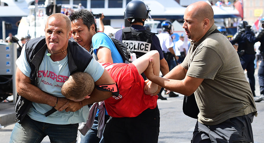 An England fan (C) is detained by police personnel following clashes between England fans and police in the city of Marseille, southern France, on June 11, 2016, ahead of the Euro 2016 football match between England and Russia