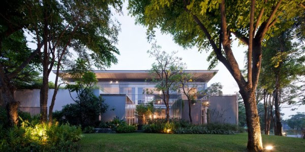 The modern house's exterior shows a boundless lawn filled with trees and greenery but no fences or walls.