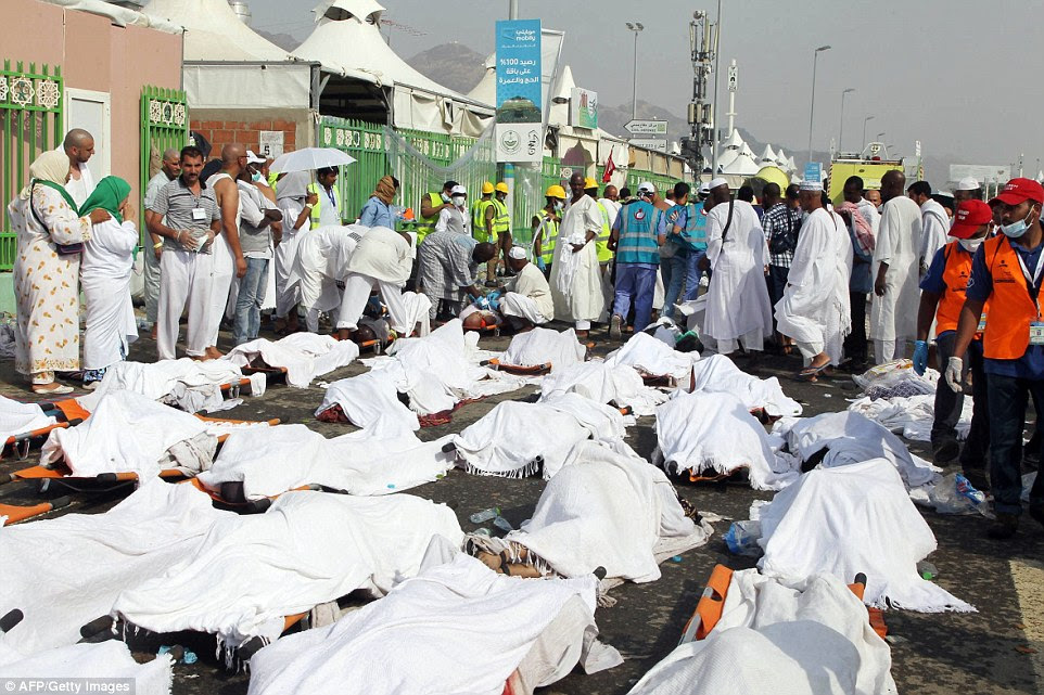 Saudi medics stand near bodies of Hajj pilgrims at the site where hundreds were killed in a stampede in Mina, near the holy city of Mecca