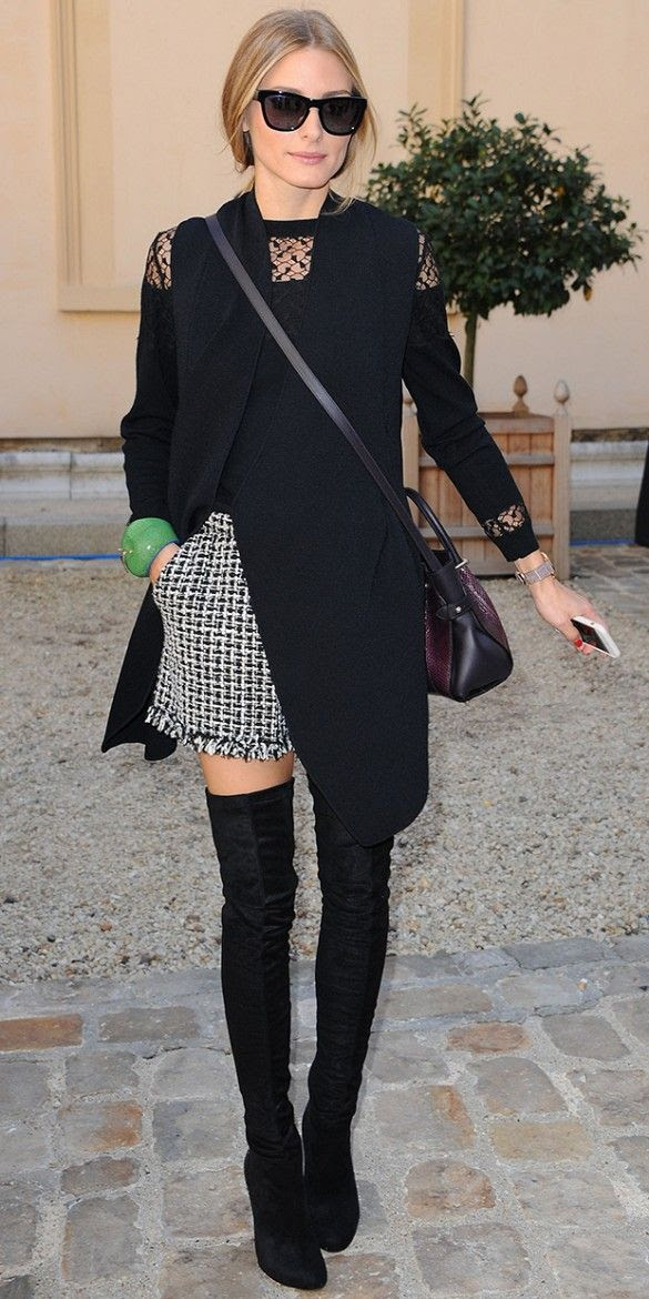 Olivia Palermo wearing a black-on-black outfit with statement shorts and over the knee boots.
