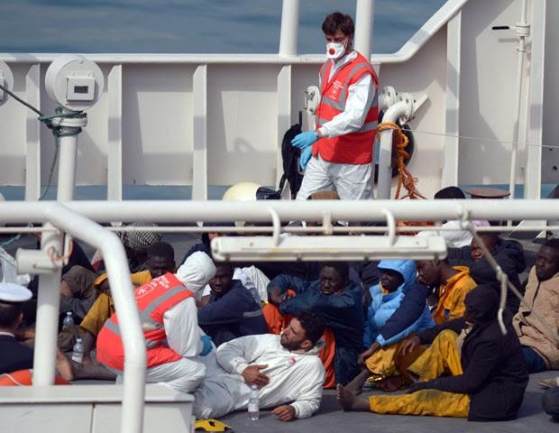 Imigrantes resgatados de naufrágio na costa da Líbia são vistos em navio de Malta nesta segunda-feira (20) (Foto: Matthew Mirabelli/AFP)