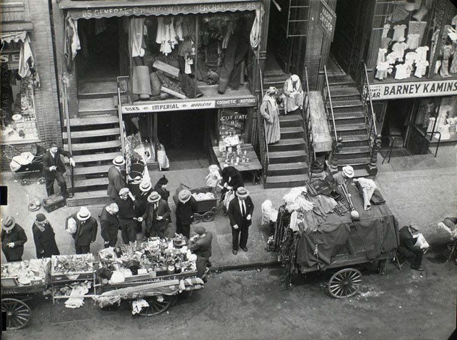 Hester Street, between Allen and Orchard Streets, Manhattan. Looking down from window on street scene including peddlers, women sitting on stoop, baby carriages, fabric and clothing stores and pedestrians.