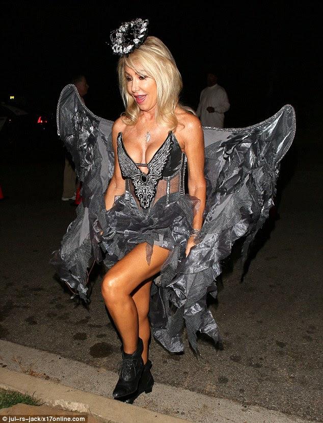 Ela caiu de onde?  Linda Thompson virou algumas cabeças no que parecia ser uma roupa de anjo cinza com asas que proporcionou uma visão clara de seu decote amplo