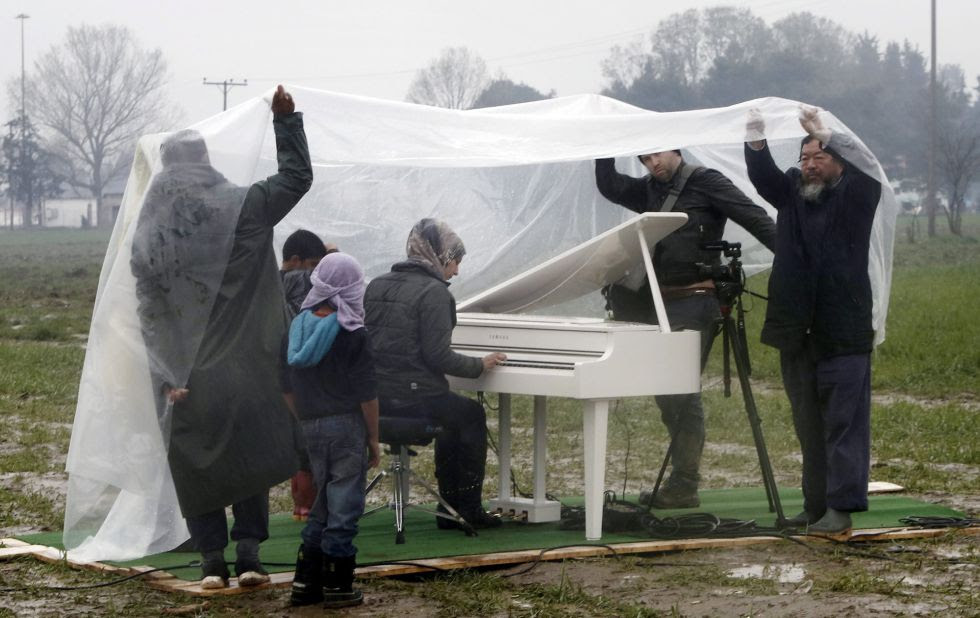 El artista Ai Weiwei (derecha) asiste a la actuación de piano de la siria Nour Al Khizam en el campo de refugiados situado en la frontera entre Grecia y Macedonia el pasado 12 de marzo.