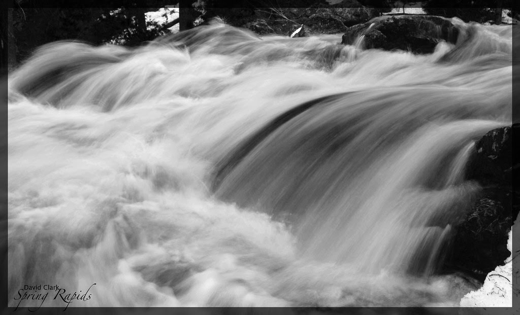 A black and white photo of a roaring river going over a small waterfall, with much foam and streaks of water.