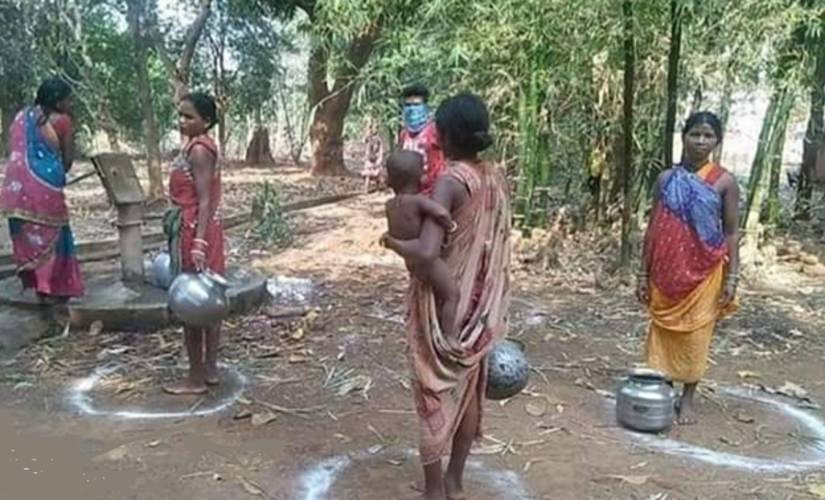 Adivasi women in Bastar maintaining social distancing while fetching water from a public borewell. Image procured by Debobrat Ghose/Firstpost