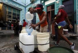Un hombre llena varios envases con agua potable procedente de un camión cisterna, en una calle de La Habana Vieja, en la capital de Cuba. Las dificultades del abastecimiento del recurso a los hogares, por problemas estructurales en la red de suministro y una aguda sequía, trastoca la vida de los habitantes de La Habana, en especial de las mujeres.