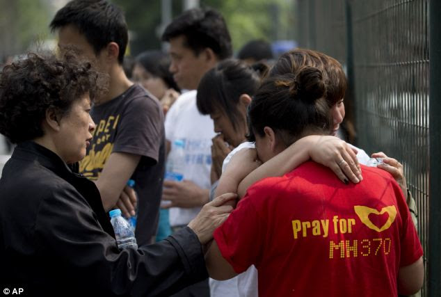 No answers: Relatives of some of the Chinese passengers on board the Malaysia Airlines flight comfort each other as they continued their sit-in protest outside the Malaysian embassy in Beijing