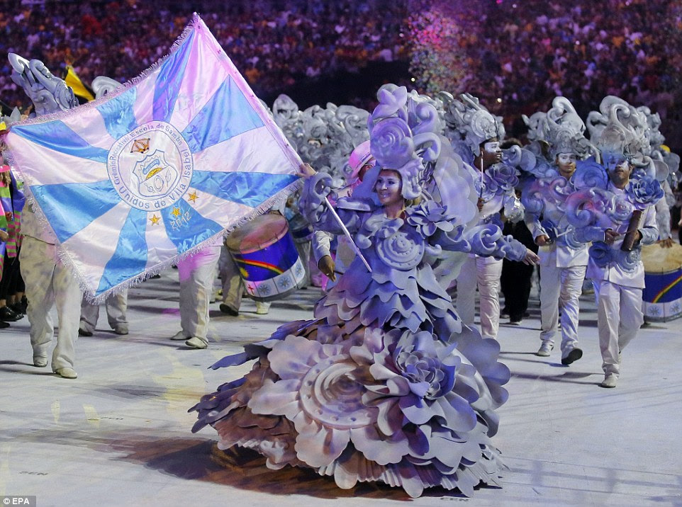 A woman, wearing a giant lilac dress waves the flag of her samba school at the event