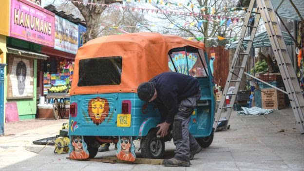 Worker puts finishing touches on a rickshaw