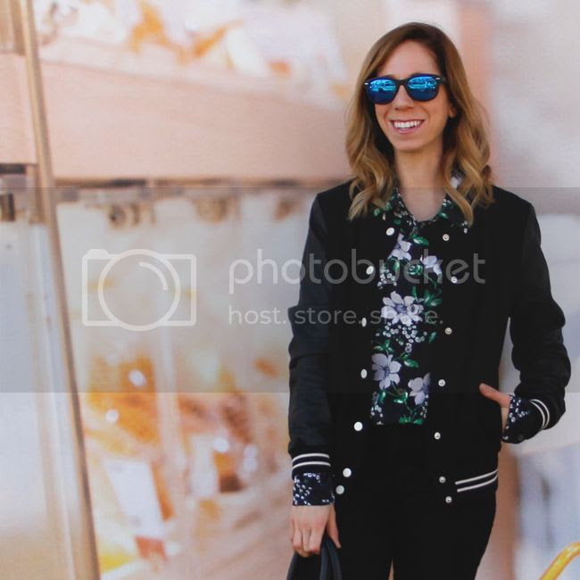 Fashion blogger The Key To Chic wears an Equipment floral silk signature blouse, Forever 21 varsity jacket, J Brand skinny jeans in black