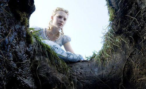 Alice (Mia Wasikowska) peeks into the rabbit hole in ALICE IN WONDERLAND.