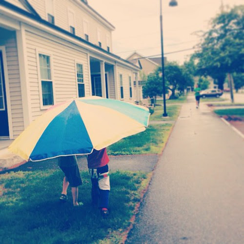 Two boys, one (giant) umbrella.