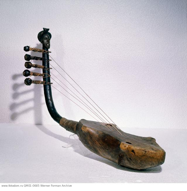 Harp with handle decoration, depicting a Mangbetu head. The hairstyles of prestigious Mangbetu groups were much imitated among neighbouring peoples, in particular the Zande. Country of Origin: Democratic Republic of Congo, Equatorial Africa. Culture: Mangbetu / Zande. Date / Period: 19th-20th C. Place of Origin: Northeastern Congo. Material Size: Wood, leather. Credit Line: Werner Forman Archive / Musee Royal de l'Afrique Centrale, Tervuren. Location: 11.