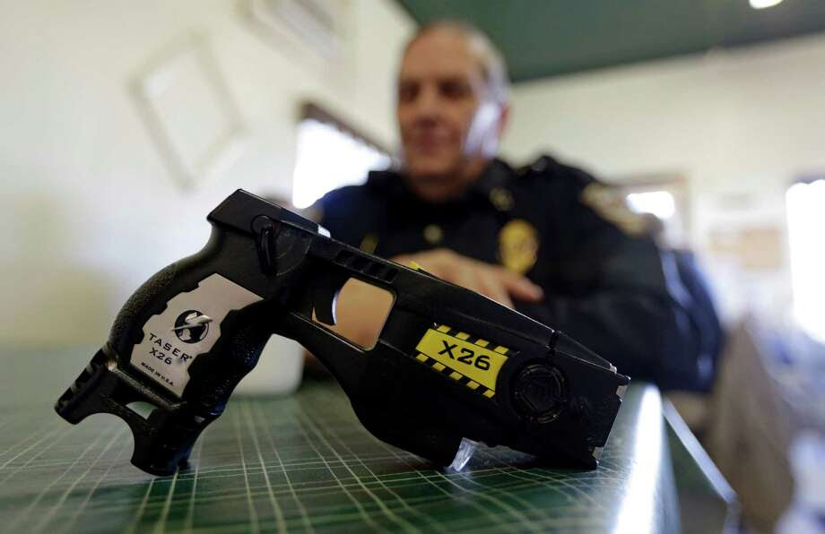 In this Nov. 14, 2013, file photo, a Taser X26 sits on a table in Knightstown, Ind. In Connecticut, a new report suggests police are more likely to use stun guns on minorities. Central Connecticut State University released its analysis Thursday, June 30, 2016, of the first statewide data of police stun gun use in the United States.  (AP Photo/Michael Conroy, File) Photo: Michael Conroy, STF / AP2013