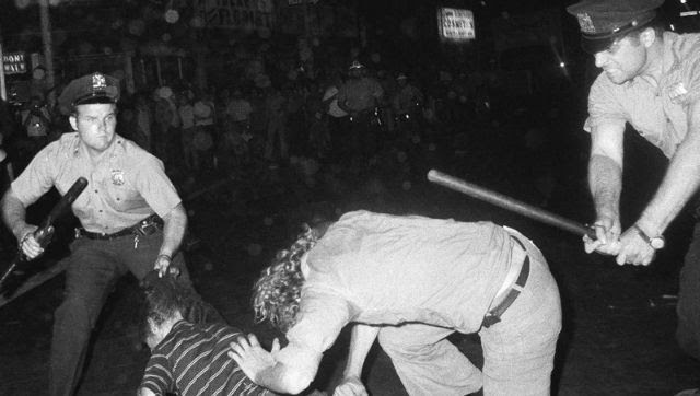 A 1970 file photo that shows an NYPD officer grabs a youth by the hair as another officer clubs a young man during a confrontation in Greenwich Village after a Gay Power march in New York. Image via The Associated Press