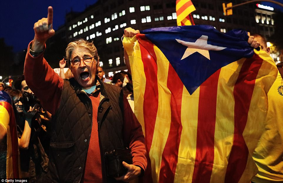 Rajoy said his government had taken the unprecedented decision to restore the law, ensure regional institutions were neutral and guarantee public services. But many Catalans, like the ones pictured, are angry at the plans