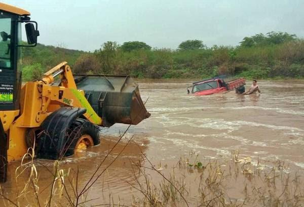 O caminhão precisou da ajuda de um trator para sair do rio.