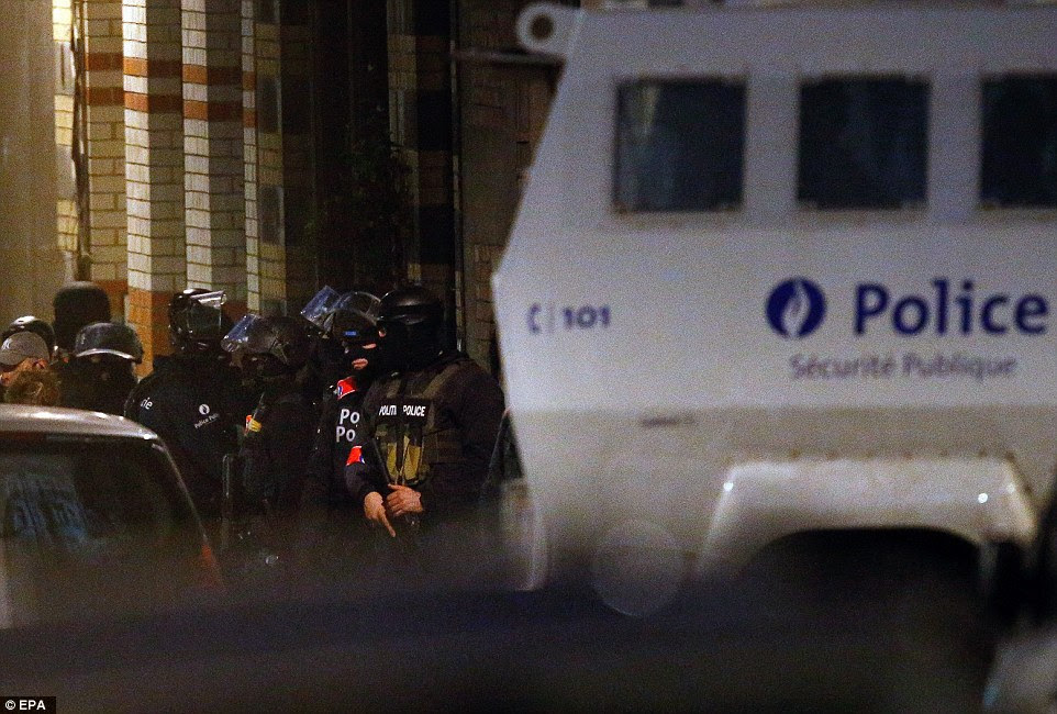Out in force: Belgian police and security personnel are seen during a series of anti-terror raids in Schaerbeek, Brussels, this evening