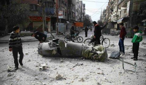 Unos niños, observando un misil tras los bombardeos en  la ciudad de Duoma en la zona de Guta Oriental, cera de Damasco.