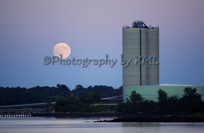 a full moon rising over the power plant