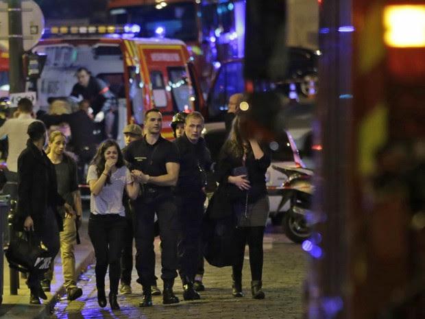 Pessoas saem em choque da casa de shows Bataclan, alvo de ataque terrorista em Paris (Foto: Kenzo Tribouillard/AFP)