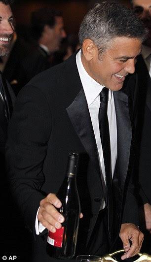 Apreciando a ocasião: Vocal partidário de Obama, George Clooney se serviu de um copo de vinho, enquanto um sorridente Kevin Spacey usava um smoking e gravata borboleta inteligente