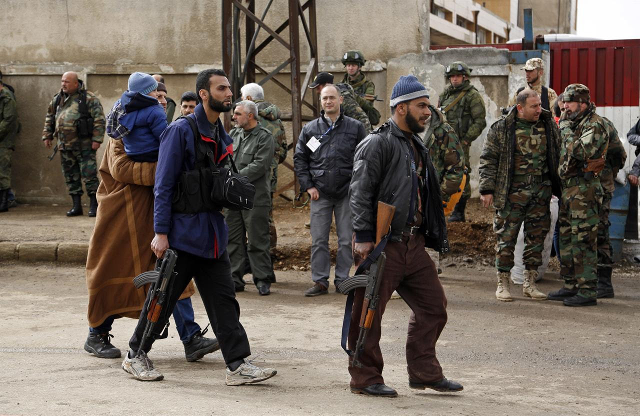 Gunmen carrying their weapons and some family members leave the al-Waer neighborhood bound for a town on the Turkish border, in Homs, Syria, Saturday, March 18, 2017. Scores of Syrian opposition fighters and their families have begun leaving al-Waer, the last rebel-held neighborhood in the central city of Homs as part of a Russian-backed evacuation deal signed earlier this week. The city was once known as the epicenter of the 2011 uprising against President Bashar Assad.