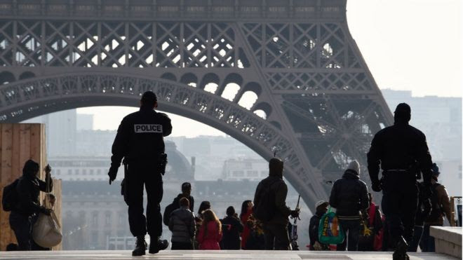 French police officers walk near the Eiffel Tower in Paris on December 24, 2015.