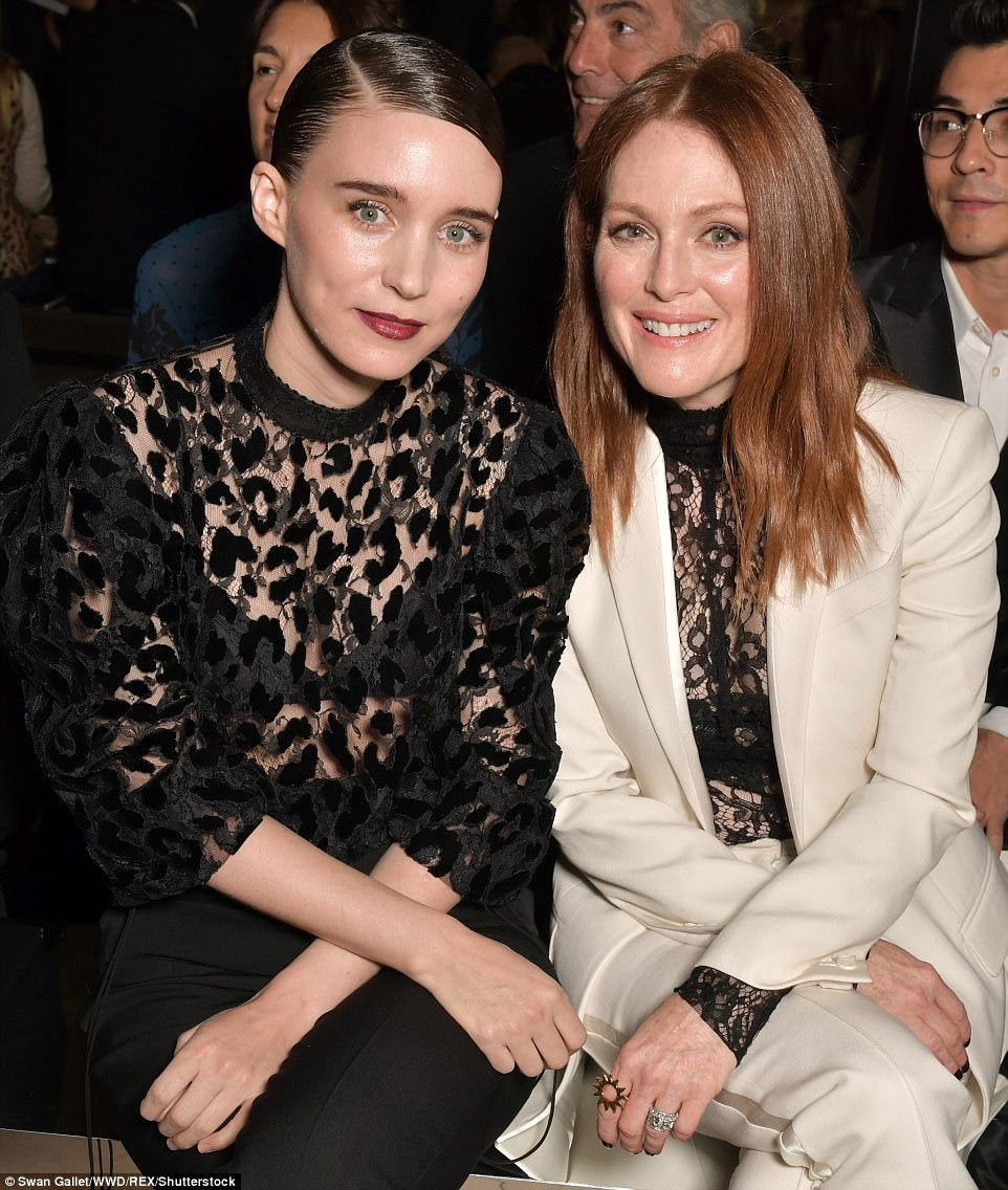 Bold: The brunette completed her androgynous look by slicking her bob to one side, and adding a deep red lipstick as she posed for cameras, before taking her place on the FROW beside Julianne Moore (R)