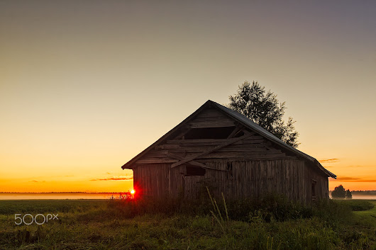 Midsummer Sunset Behind A Barn House