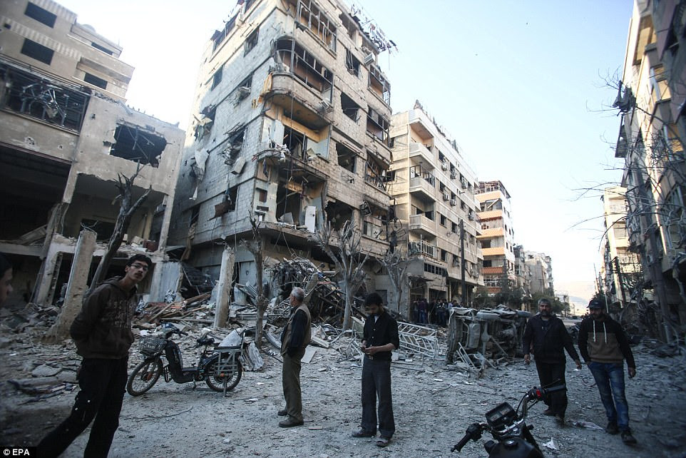 People inspect damaged buildings after an airstrike in Douma, Syria on Friday - just hours after US missiles struck the Shayrat miltiary base