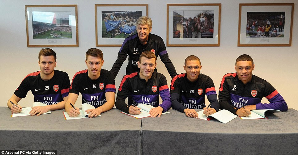 Manager Arsene Wenger of Arsenal stands over (L-R) Carl Jenkinson, Aaron Ramsey, Jack Wilshere, Kieran Gibbs and Alex Oxlade-Chamberlain