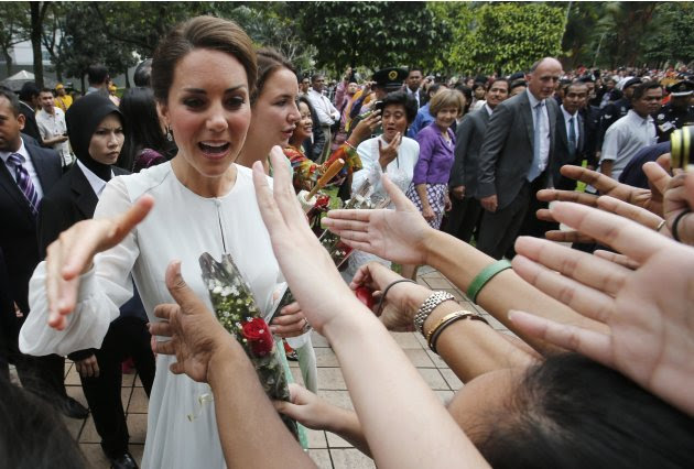 Catherine, Britain's Duchess of Cambridge, shakes hands with well-wishers at KLCC Park in Kuala Lumpur