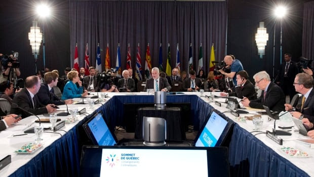 Quebec Premier Philippe Couillard, centre, speaks at the beginning of a premiers' summit on climate change Tuesday in Quebec City.