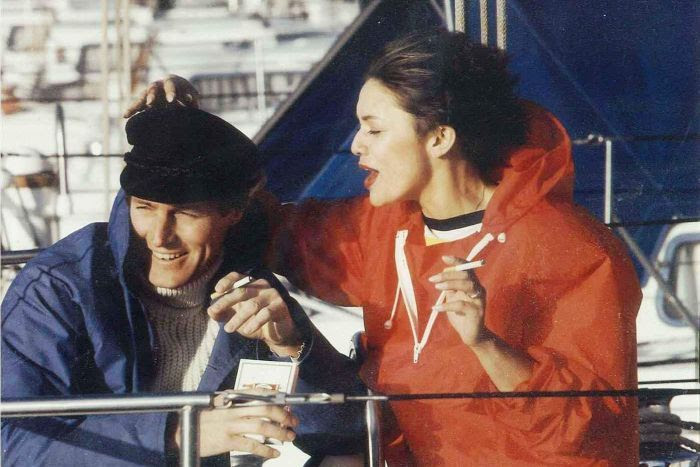 A woman and a man smoke cigarettes on a yacht.
