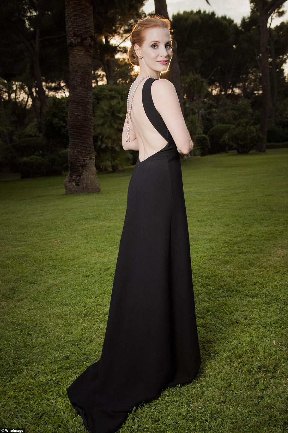 Glowing: Jessica Chastain olhou elegante em um assoalho-varrendo vestido preto com um colar de pérolas