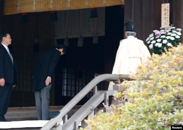 日本首相安倍晋三12月26日参拜靖国神社时在神道祭司旁鞠躬。