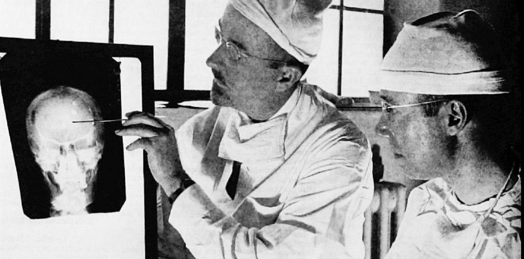 Le Dr Walter Freeman, accompagné du DrJames W. Watts,étudie une radio avant de réaliser une lobotomie.Photo du Saturday Evening Post du 24 mai 1941. | Studio Harris & Ewing via Wikimedia Commons