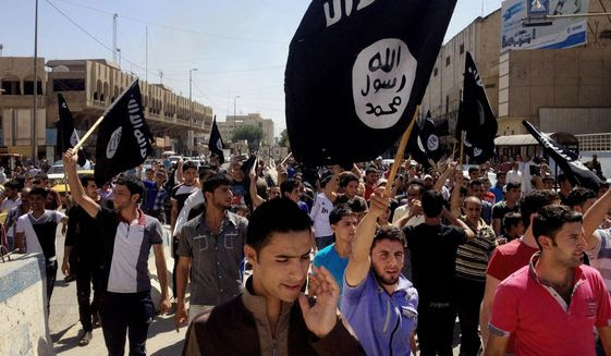 Demonstrators chant pro-Islamic State group slogans as they wave the group's flags in front of the provincial government headquarters in Mosul, 225 miles (360 kilometers) northwest of Baghdad on June 16, 2014. (Associated Press) **FILE**