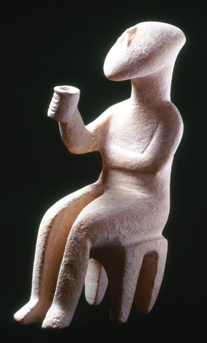 Μαρμάρινο ειδώλιο καθιστής μορφής. Ο «εγείρων πρόποσιν».Πρωτοκυκλαδική ΙΙ περίοδος (περ. 2700-2400/2300 π.Χ.)Συλλογή Ν.Π. Γουλανδρή, αρ. 286