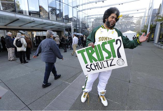 "Kris Brannon, who is known as ""Sonics Guy"" for his efforts to bring an NBA basketball team back to Seattle, holds a sign that reads ""Trust Schultz?"" as he greets attendees arriving"