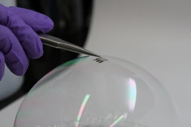 MIT researchers place a lightweight solar cell on top of a soap bubble. Image source: Joel Jean and Anna Osherov.