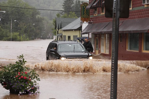 A security guard hangs on the door of Gov. Andrew Cuomo's SUV in the middle of a flooded street Sunday, Aug. 28, 2011, in Margaretville, N.Y. Gov. Cuomo was riding in the SUV, and posted some photos o