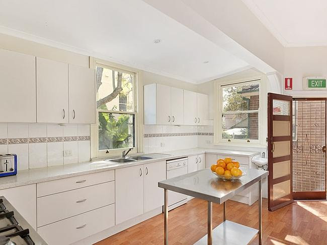 The kitchen features modern appliances, stone benches and built-in storage.