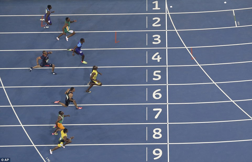 Bolt powers across the finish line ahead of his rivals to win his third consecutive Olympic 100m gold medal
